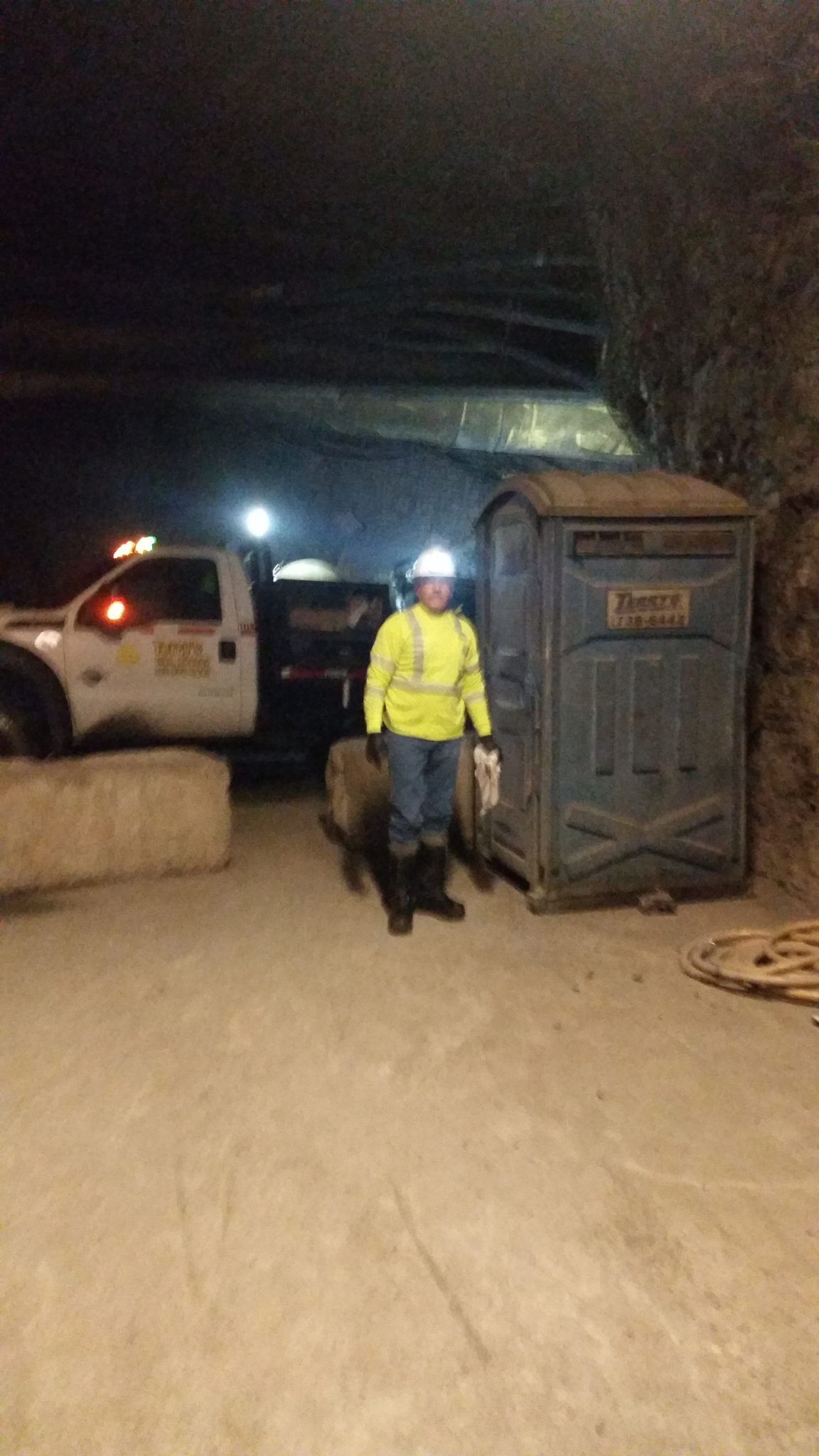 Domingo Garcia, the underground service technician, wears reflective clothing and a miner's lamp to illuminate units located 1,500 feet underground.
