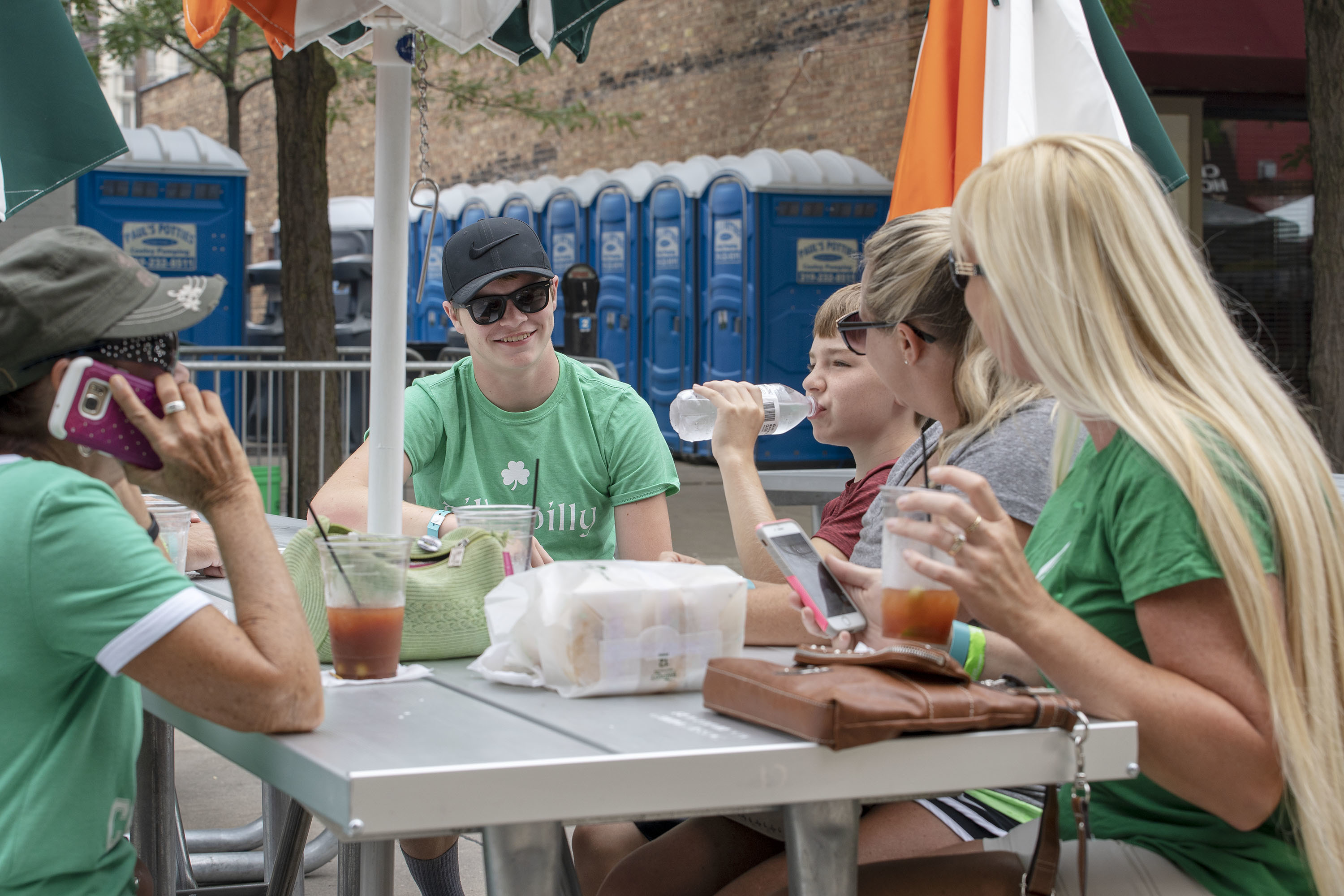 A family eats and drinks near a restroom station installed by Cooley's Pumping at the Iowa Irish Festival in Waterloo. –Photos by K.C. McGinnis