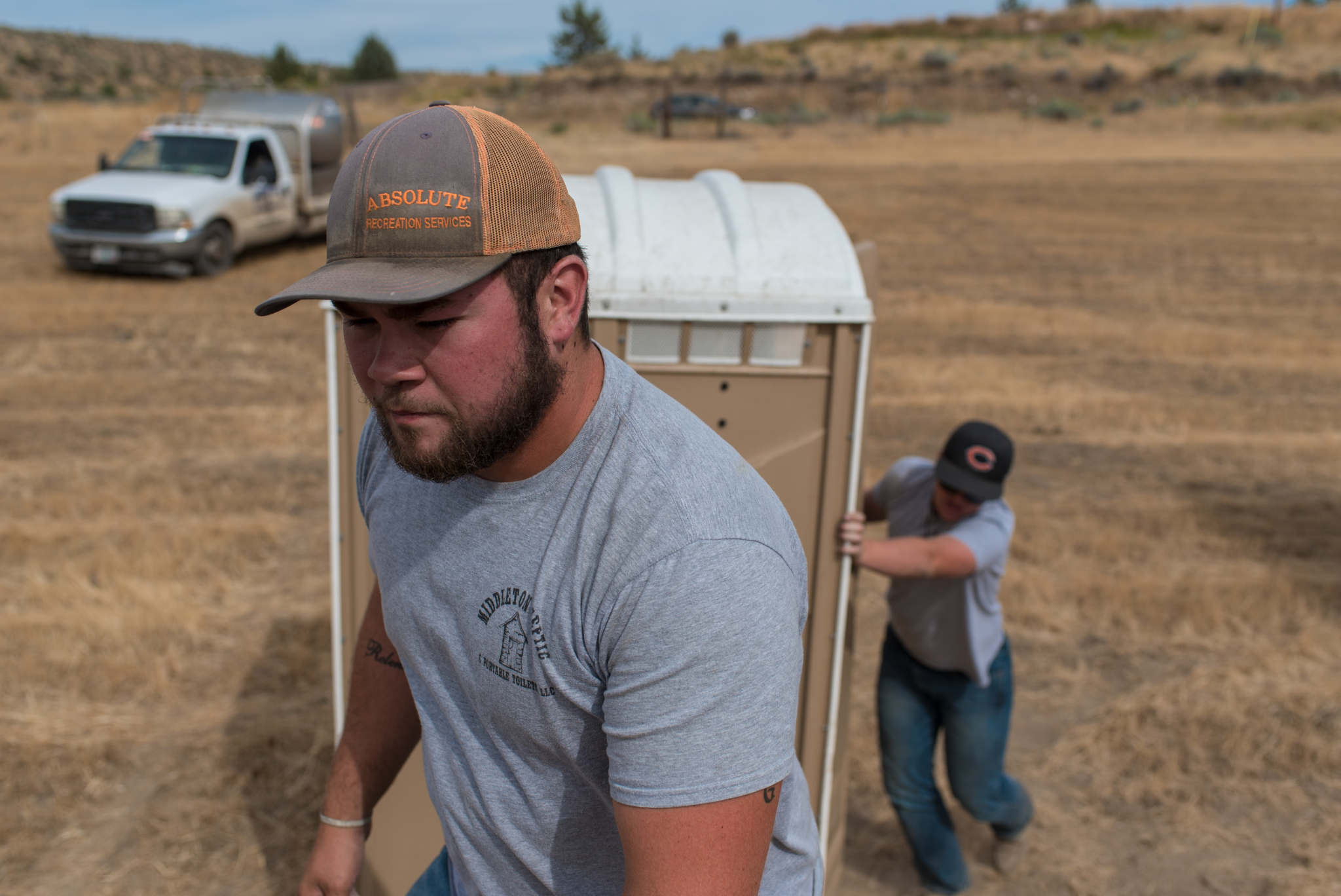 Middleton Septic & Portable Toilets employees Zach Lofting (right) and Kyler Cox unload 10 portable toilets in a local farm field Aug. 14, 2017 in Madras.  –Photos by Ethan Rocke