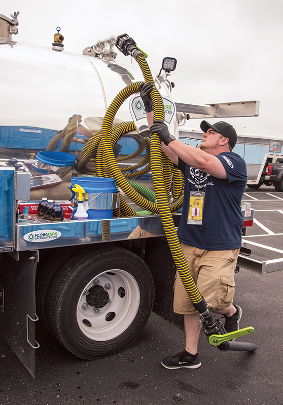 Ty Springer returns the suction hose to the hanger on a truck built out by FlowMark Vacuum Trucks.