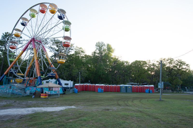 Portable restrooms and sinks positioned near a Ferris wheel at the Wanee Music Festival in Live Oak, Forida. (Photo by Rob Herrera)